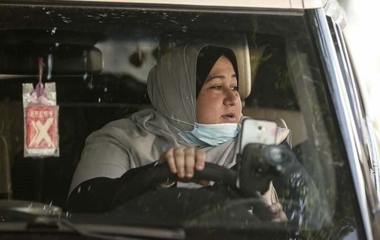 La primera mujer taxista palestina de la Franja de Gaza, Nayla Abu Jubbah, de 39 años, está sentada junto a su vehículo mientras trabaja en la ciudad de Gaza.
