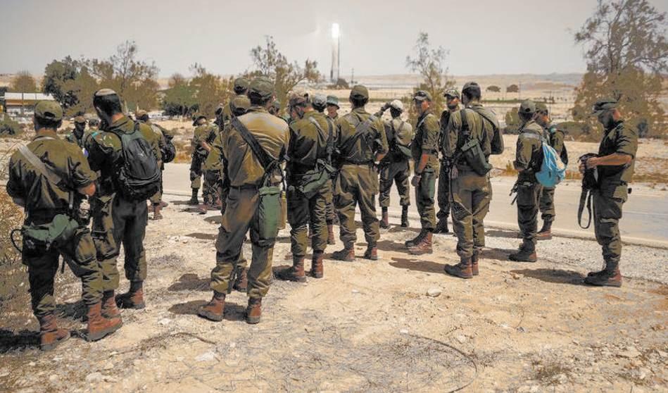 Soldados israelíes se reúnen mientras inspeccionan la zona tras la explosión de un misil cerca de la instalación nuclear de Dimona.